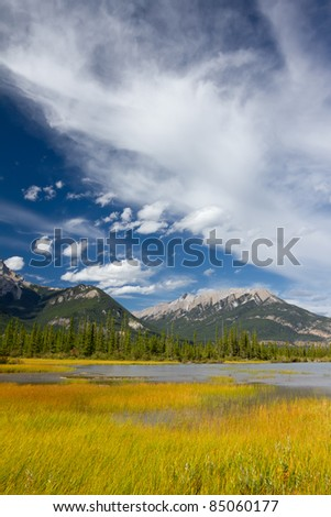 Beautiful Canadian Landscape: Swampy Lake, Rocky Mountains and Cloudy Sky. Photo is taken in Jasper National Park, Alberta, Canada - stock photo