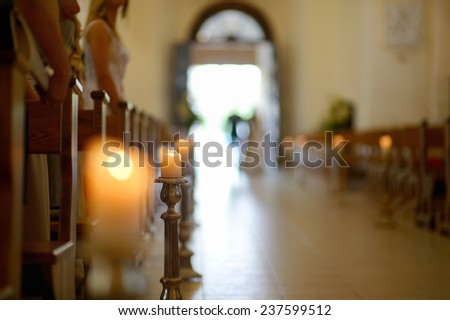 Beautiful candle wedding decoration in a church during wedding ceremony - stock photo