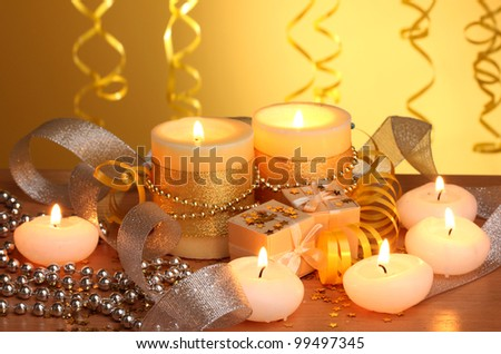 Beautiful candles, gifts and decor on wooden table on yellow background