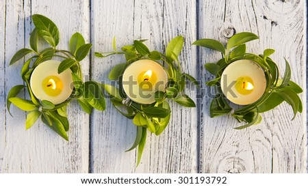 Beautiful candles with flowers on wooden background - stock photo