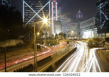 beautiful car trails with the building, red blue and yellow light moving on the road in hong kong business centre - stock photo