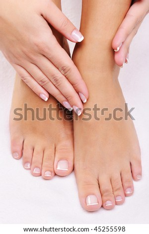 Beautiful care female feet with the hand with a French manicure - stock photo