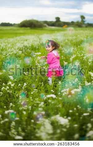 beautiful carefree girl playing outdoors in field with high green grass. little child running away from bubbles and laughing - stock photo