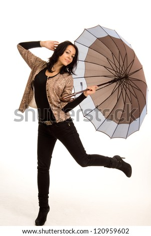 Beautiful carefree playful young girl with an umbrella in stylish clothing kicking her foot up in the air, isolated on white - stock photo