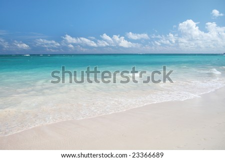 Beautiful Caribbean tropical beach with white sand and green ocean, suitable background for a variety of designs. FOCUS on the waves rolling onto the beach - stock photo