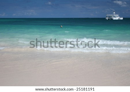 Beautiful Caribbean tropical beach with white sand and green ocean, suitable background for a variety of designs (focus on waves rolling onto the beach) - stock photo