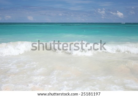 Beautiful Caribbean tropical beach with white sand and green ocean, suitable background for a variety of designs (focus on waves rolling onto shore) - stock photo