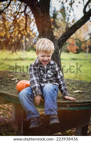 Beautiful casual blond child sitting outdoor on table and laughing. Autumn. Outdoor portrait  - stock photo