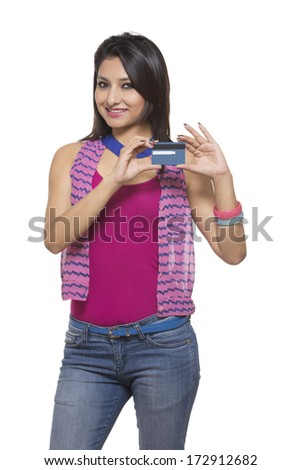 Beautiful casual girl holding a credit card on white background.