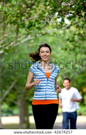 Beautiful casual girl running at the park - stock photo