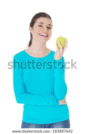 Beautiful casual woman holding an apple. Isolated on white.