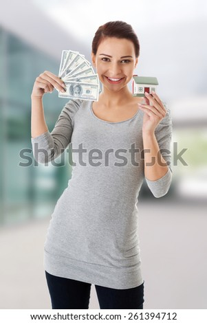 Beautiful casual woman holding money and house - stock photo