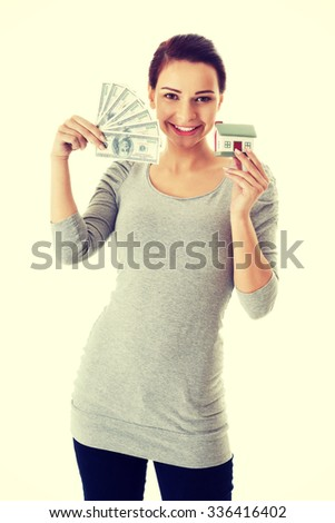 Beautiful casual woman holding money and house