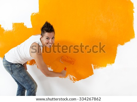 Beautiful, casual woman painting a white wall with orange color. She is looking into the camera with a friendly smile.