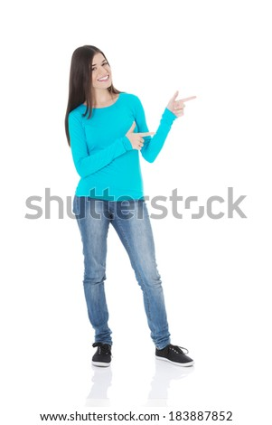 Beautiful casual woman pointing on copy space. Isolated on white.  - stock photo