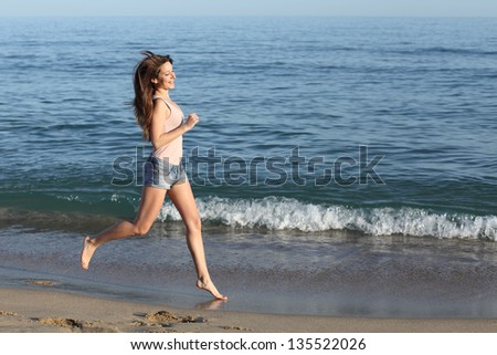 Beautiful casual woman running alone on the beach shore near the water