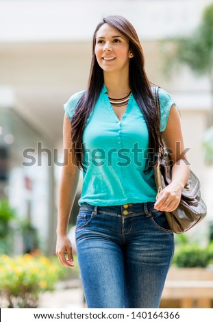 Beautiful casual woman walking outdoors and looking happy - stock photo