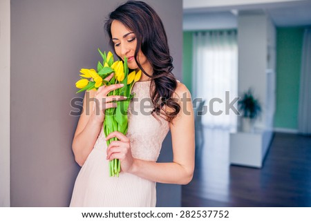 Beautiful casual woman with a tulip bouquet in front of a grey wall - stock photo