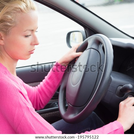 Beautiful casually dressed female car driver starting the engine.