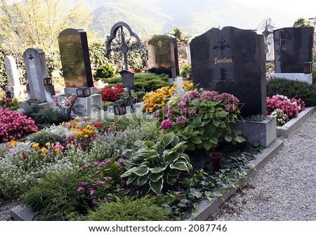 Beautiful catholic graves with many flowers - stock photo