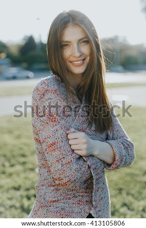 Beautiful caucasian attractive charming young lady model posing happy on sunset, play with hair, making funny faces and smiles to the camera on a grass in the park - stock photo