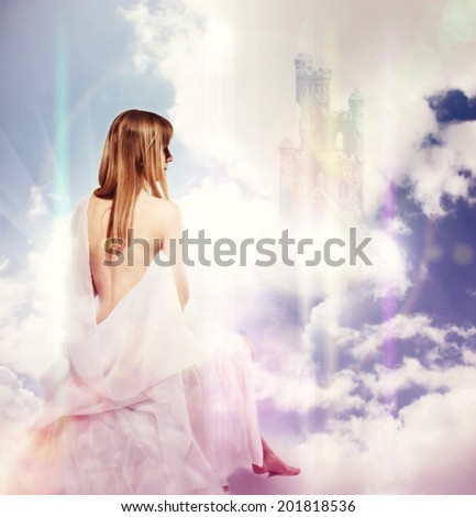Beautiful caucasian blond girl is sitting on the clouds in white cloth with naked back and shoulder - stock photo