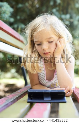 Beautiful Caucasian blond girl lying on old park bench with smart phone watching movie - stock photo