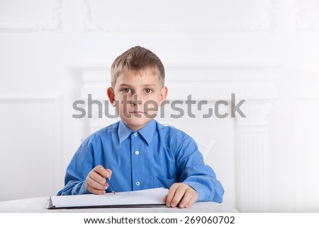 beautiful, caucasian boy draws a pencil on the album  - stock photo