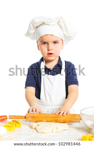 Beautiful caucasian boy making a cake, isolated on white background. Vertical view