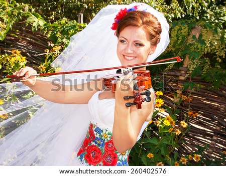 Beautiful caucasian bride in the dress and the bridal veil in the ukrainian style is playing the violin. Happy smiling (laughing) attractive girl is holding fiddle. Ukraine. Wedding concept. Close up. - stock photo