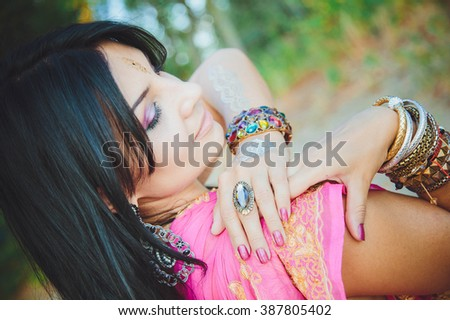 Beautiful caucasian brunette woman in dress in oriental style with oriental patterns on the hands and face , with numerous bracelets. Indian woman - stock photo