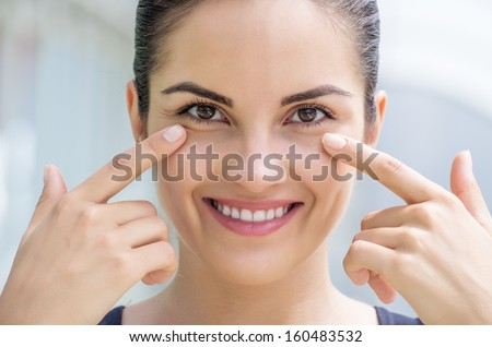 Beautiful caucasian brunette young woman touching the skin under her eye. - stock photo