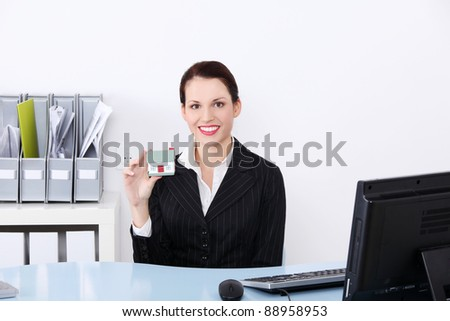 Beautiful caucasian businesswoman sitting in the office holding little house.