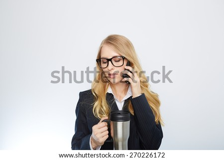 Beautiful caucasian businesswoman talking on phone holding a coffee against white background - stock photo