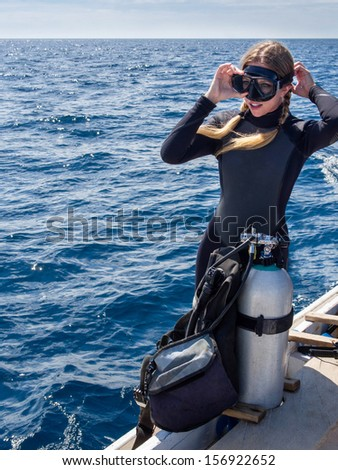 Beautiful, Caucasian diver on a boat in the ocean putting on goggles in preparation for scuba diving. - stock photo