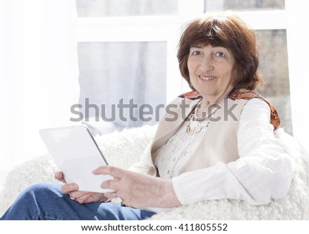 Beautiful Caucasian elderly woman 80 years old. He is sitting in armchair with a tablet computer. Smiling and looking into the lens. Horizontal color image. Light background - stock photo