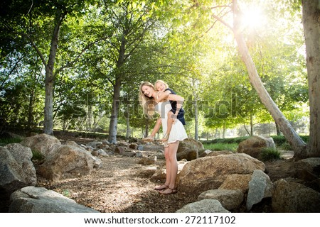 Beautiful Caucasian ethnicity mother and daughter having fun at park - stock photo