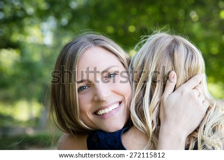 Beautiful Caucasian ethnicity mother and daughter hugging and bonding at park - stock photo