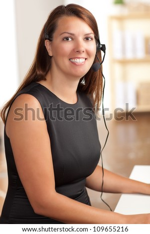 Beautiful Caucasian female at work wearing a sleeveless black dress with brunette hair.