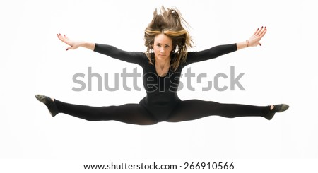 beautiful caucasian female dancer jumping and doing split up in the air, on white background - stock photo