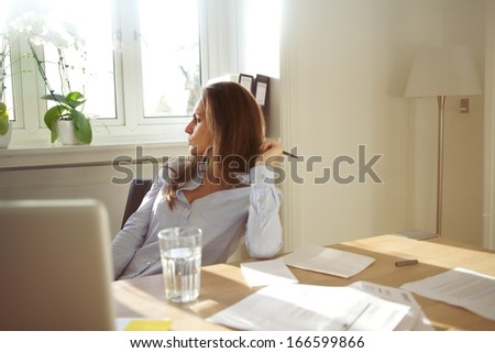 Beautiful caucasian female sitting at table with glass of water, documents and laptop. Business woman in home office looking away thinking. - stock photo