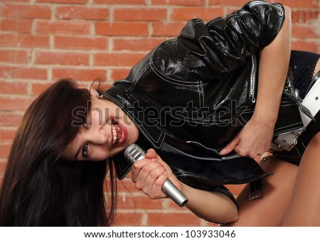 Beautiful Caucasian female with a microphone singing against a brick wall