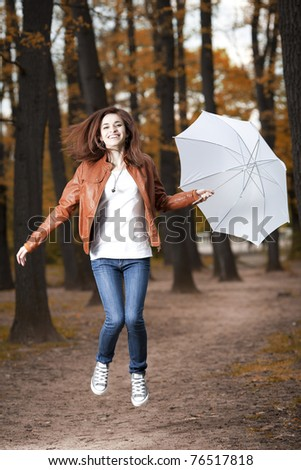 Beautiful caucasian girl jumping in forest with umbrella
