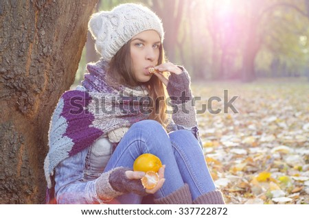 Beautiful Caucasian girl sitting on autumn leaves in park and eating tangerine  - stock photo