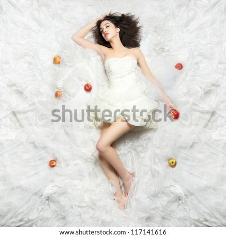 Beautiful Caucasian girl sleeping after eating the forbidden fruit. Photographed from above - stock photo