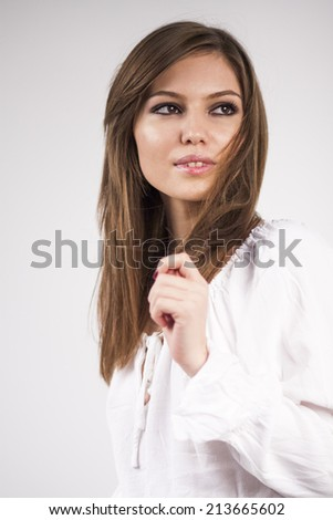Beautiful caucasian girl wearing a white blouse with light grey background