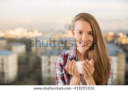 Beautiful caucasian girl with side swept hair drinking coffee on blurry city background - stock photo