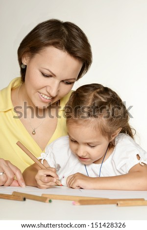 beautiful Caucasian mom with her daughter sitting at the table with a pencil