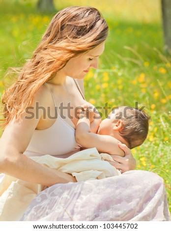 Beautiful Caucasian Mother Breastfeeding Baby Son Outdoors In Summer