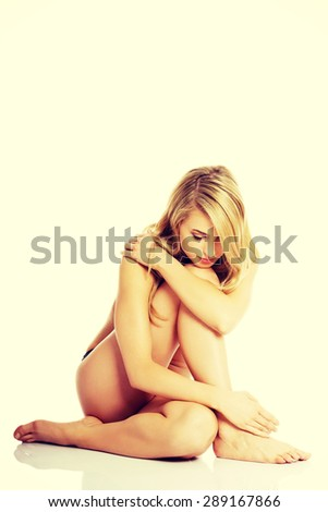 Beautiful caucasian naked woman sitting with fresh clean skin. - stock photo